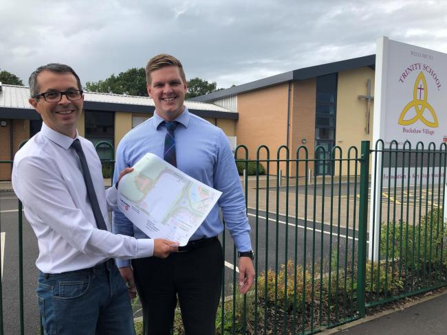 County Councillor Aidy Riggott and Luke Kerr with the plan for yellow lines near the school