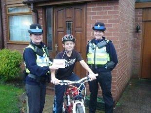 PCSO Maria Fetherstone (left) and PCSO Liz Harrison handing Joseph Lyth one of the packs