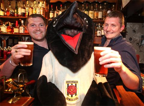 Glen Hutchinson, left, and Seb Draper from The Spinners with Chorley FC's Victor The Magpie