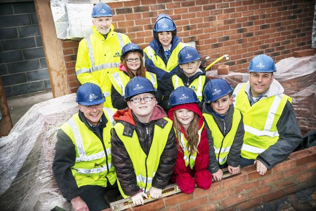 LAYING FOUNDATIONS: Coppull Primary pupils at the site with Morris Homes staff