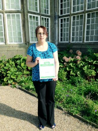 top reviews: Coun Bev Murray showing the excellence certificate at Astley Hall