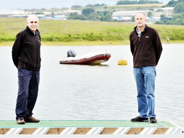 Sailing club member Geoff Peake, left, and captain Dave Anderson with a boat similar to the one that was stolen