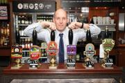 POSTAL VOTING: The manager of the Postal Order pub in Blackburn, Andrew Ibbotson, with some of the festive ales on offer over his bar this Christmas
