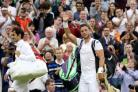 Marcus Willis waves as he leaves centre court with Roger Federer