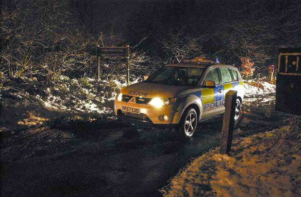 CRIME SCENE: A police car at the entrance to the car park near Anglezarke Reservoir where the man's body was found