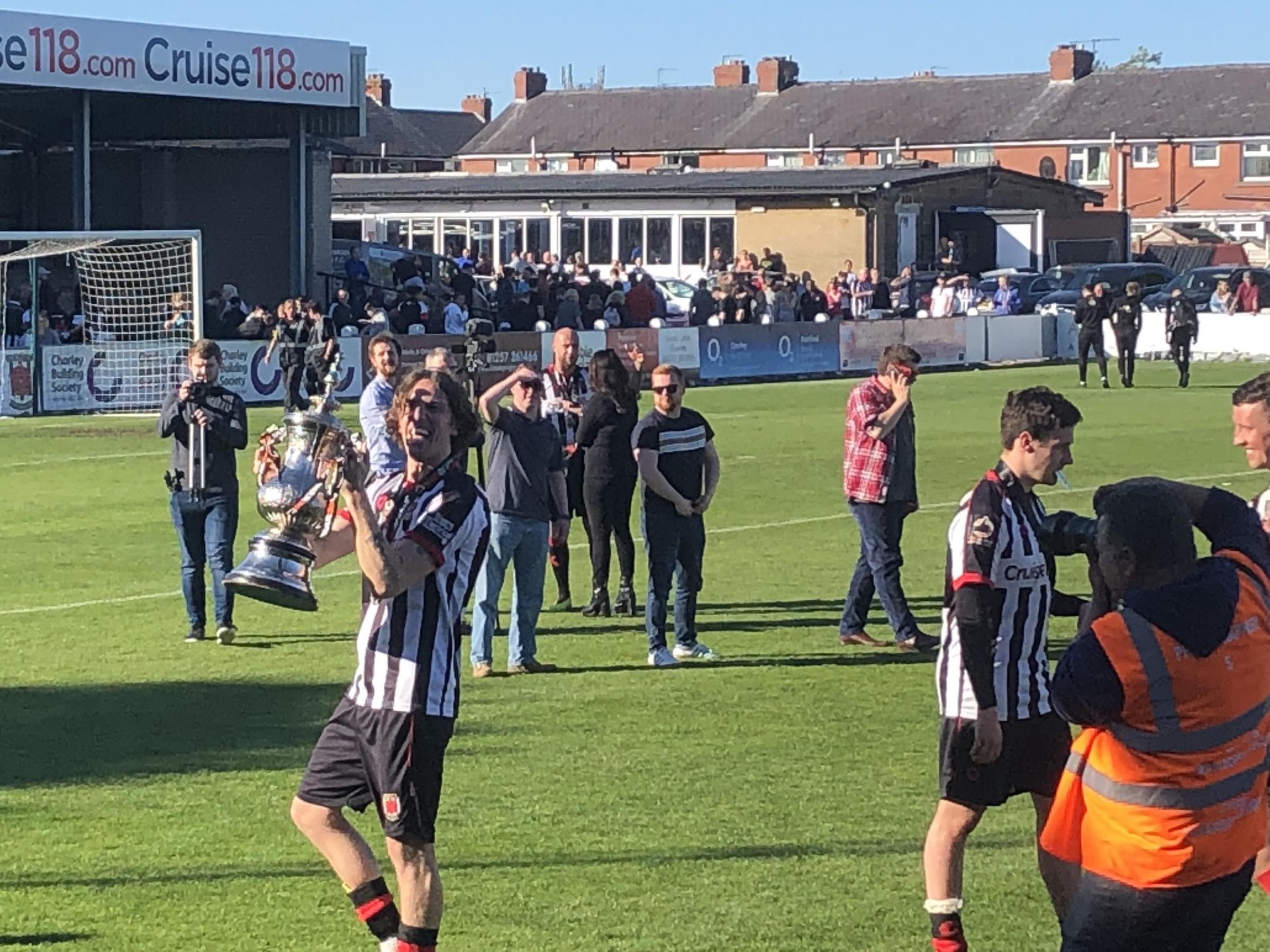Josh Wilson shows off the National League North promotion trophy following Chorley's dramatic spot kick win