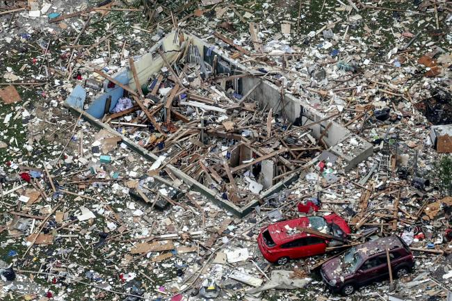 Damaged vehicles in the debris of a home explosion in Jeffersonville, Indiana